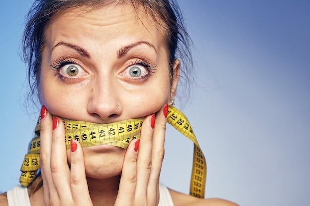 입술에 녹화 테이프를 가진 젊은 여자. 그녀는 다이어트에 대해 걱정하고 있습니다.