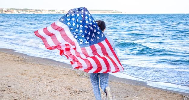 アメリカの国旗を持った若い女性が海を走っています。愛国心と独立記念日のお祝いの概念。