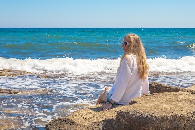 白いチュニックに金髪の若い女性が波で海のそばの石の上に座っています。旅行と観光、海岸での夏休み。