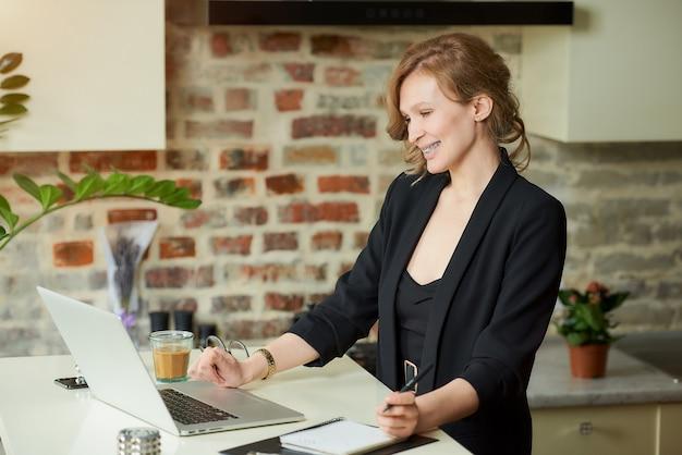 Молодая женщина с брекетами работает удаленно на своей кухне. женский босс, улыбаясь на видео-конференции с ее сотрудниками у себя дома. учительница счастлива со студентами на онлайн лекции.
