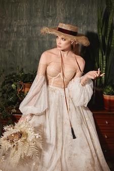 Молодая женщина со свадебным макияжем в модном свадебном платье и соломенной шляпе красивая модель девушка с ...