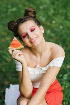 明るい化粧をした若い女性が目を閉じ、笑顔を浮かべ、彼女の手にスイカのスライスを保持している