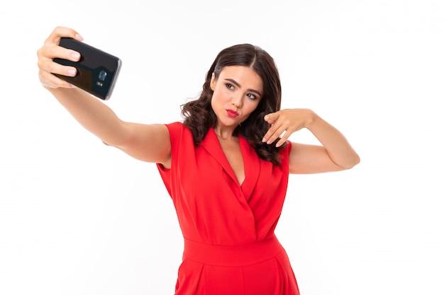 빨간 여름 드레스에 밝은 화장으로 젊은 여자 손에 전화와 함께 서 고 selfie