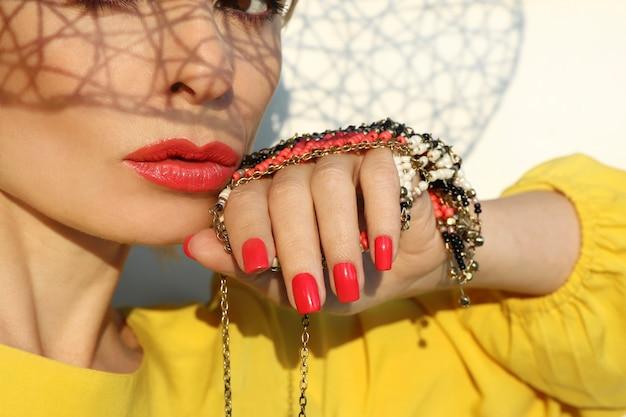 彼女の顔に影のパターンで明るい背景に黄色のドレスで珊瑚の唇と爪を持つ若い女性。