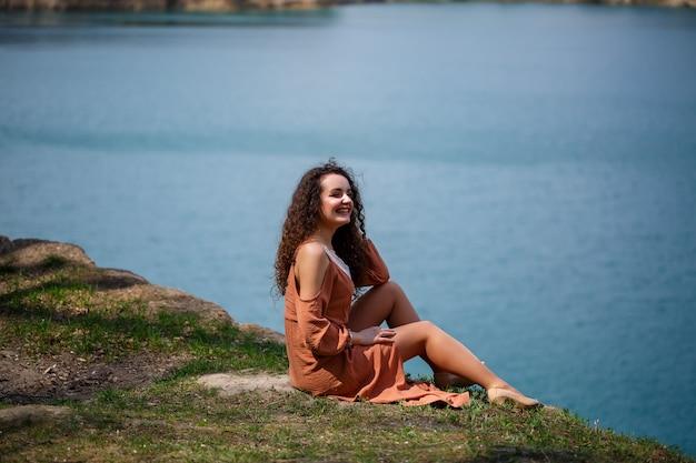 青い湖を背景にした緑の牧草地に、巻き毛と笑顔の若い女性が座っています。暖かい夏の日、幸せな女の子、喜びの感情