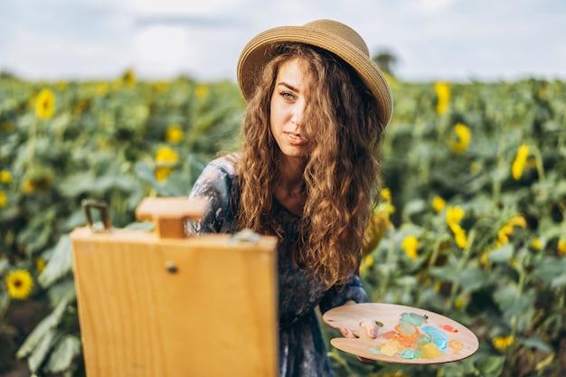 Молодая женщина с вьющимися волосами и в шляпе рисует в природе. женщина стоит в поле подсолнечника в прекрасный день