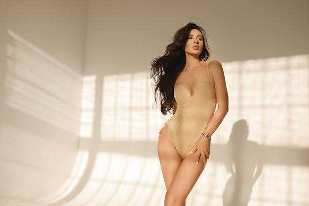 Молодая женщина с пухлыми губами и идеальным телом в бежевом нижнем белье позирует в помещении