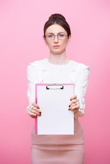 眼鏡をかけた若い女性がクリップボードのフォルダーを手に持っています