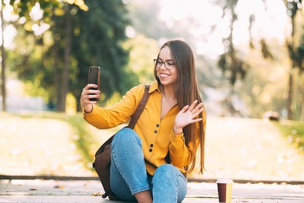 Молодая женщина в очках улыбается и машет на свой телефон, сидя где-то на природе на улице