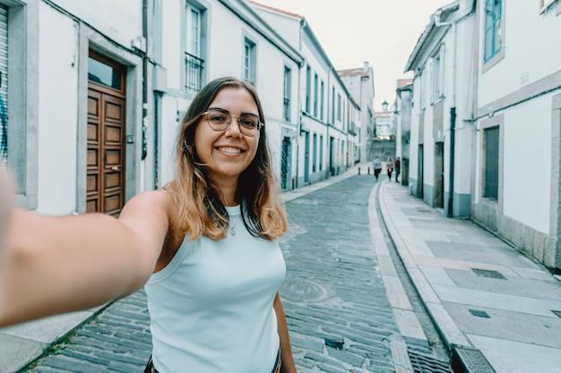 Молодая женщина в очках делает селфи на старой испанской улице