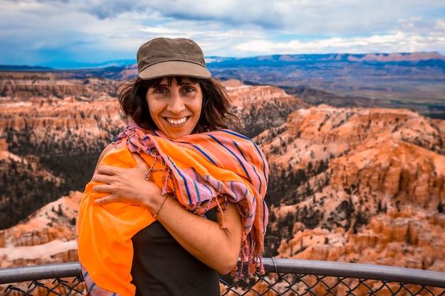 Молодая женщина в зеленой рубашке смотрит на национальный парк из брайс-пойнт в национальном парке брайс. юта, сша