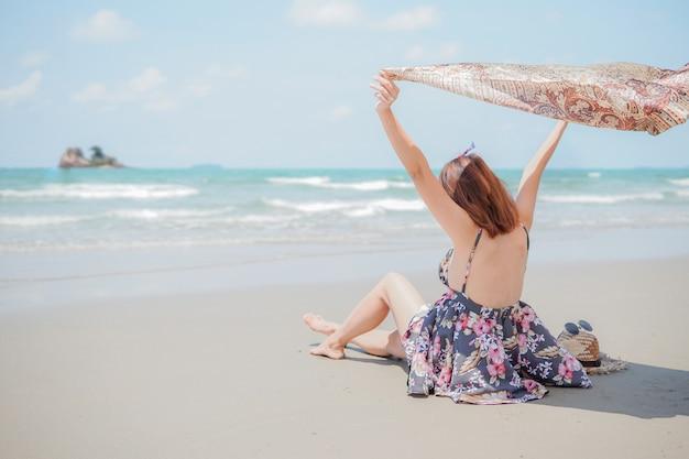 모자와 선글라스 해변에 앉아 젊은 여자
