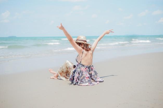 모자와 함께 젊은 여성이 해변에 앉아