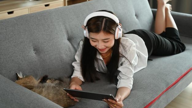 時間を楽しんで、リビングルームでタブレットでリラックスしてソファに横になっているヘッドフォンを持つ若い女性。