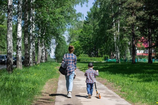 Молодая женщина с ребенком в одинаковой одежде из джинсовых джинсов и синих клетчатых рубашек гуляет по парку с березками.