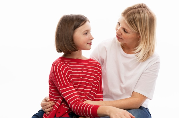 Молодая женщина с дочерью-подростком обнимает и нежно смотрит друг на друга. белая стена.