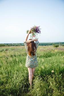 カラフルなショートドレスを着た長い髪の若い女性は、立っている挙手で花束を持っています...