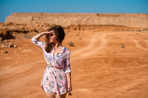 Молодая женщина с длинными волосами в коротком платье гуляет по оранжевой каменистой пустыне в жаркий день.