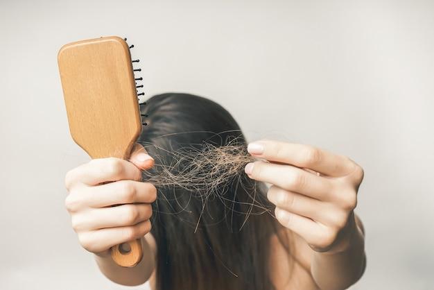 긴 머리를 가진 젊은 여성은 탈모로 짜증이 나며, 빗과 머리카락을 손에 들고 눈을 숨깁니다