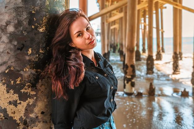 Молодая женщина с длинными волосами стоит под пирсом на пляже малибу в калифорнии.