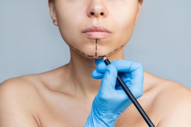 턱에 표시가 있는 젊은 여성 의사 장갑 낀 손으로 환자 얼굴에 표시
