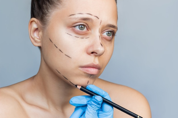 그녀의 얼굴에 표시가 있는 젊은 여성 의사의 장갑을 낀 손이 환자의 턱에 표시를 합니다.