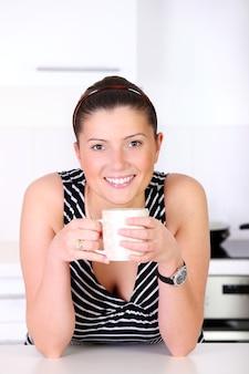 Молодая женщина с утренним кофе на кухне