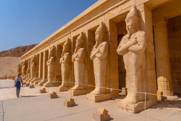 ルクソールにあるハトシェプスト女王の葬祭殿に入るファラオの彫刻を持つ若い女性。エジプト