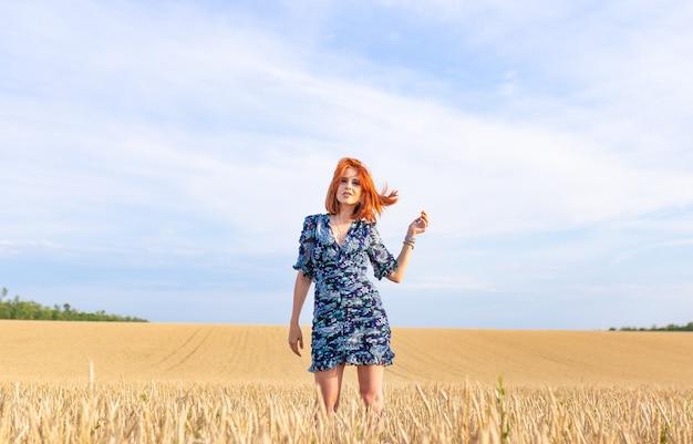빨간 버건디 머리를 한 젊은 여성이 드레스를 입고 밀밭 한가운데에 앉아 명상하고 생각합니다