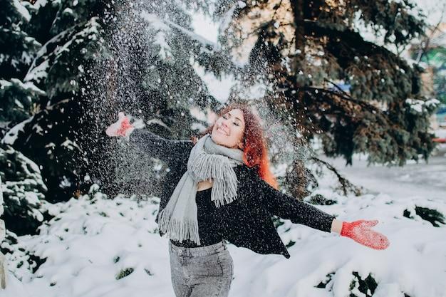 Молодая женщина с рыжими волосами бросает снег в воздух в солнечный зимний день зимний праздник