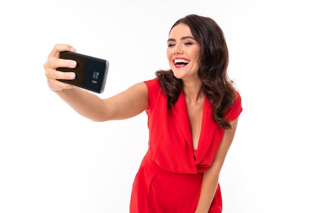 빨간 여름 드레스에 빨간 입술, 밝은 화장, 눈부신 미소, 어두운 물결 모양의 긴 머리를 가진 젊은 여자가 서서 그녀의 전화에 셀카를 찍습니다.