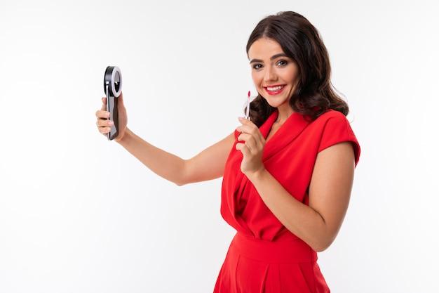 빨간 옷을 입은 빨간 입술, 밝은 화장, 검은 물결 모양의 긴 머리를 가진 젊은 여성이 전화, 빨간 립스틱으로 서서 셀카를 찍습니다.