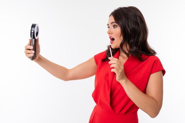 붉은 입술을 가진 젊은 여자는 링 램프와 휴대 전화 카메라에 화장을
