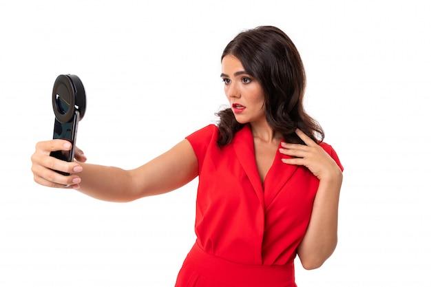 붉은 입술을 가진 젊은 여자는 전화 및 링 램프와 셀카를 할