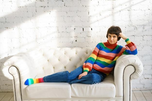 Молодая женщина с короткими волосами в радужном свитере и носках сидит на белом диване, концепция сексуальных меньшинств