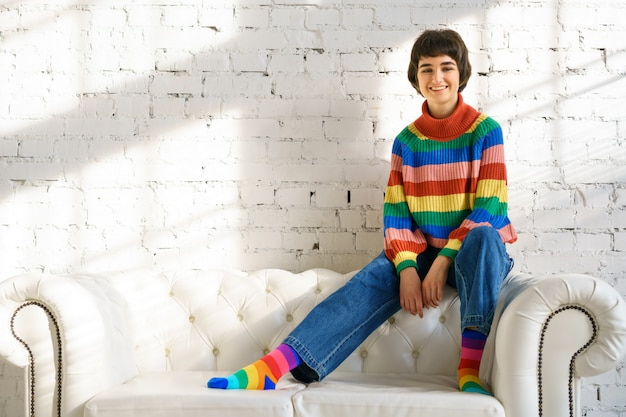 Молодая женщина с короткими волосами в радужном свитере и носках сидит на белом диване