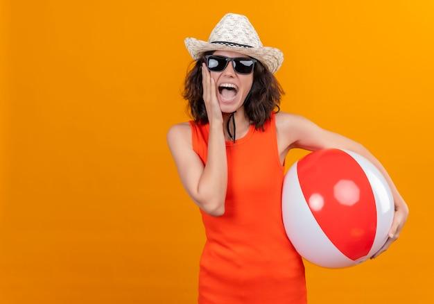 Молодая женщина с короткими волосами в оранжевой рубашке в шляпе от солнца и солнечных очках держит надувной мяч и держит руку на лице