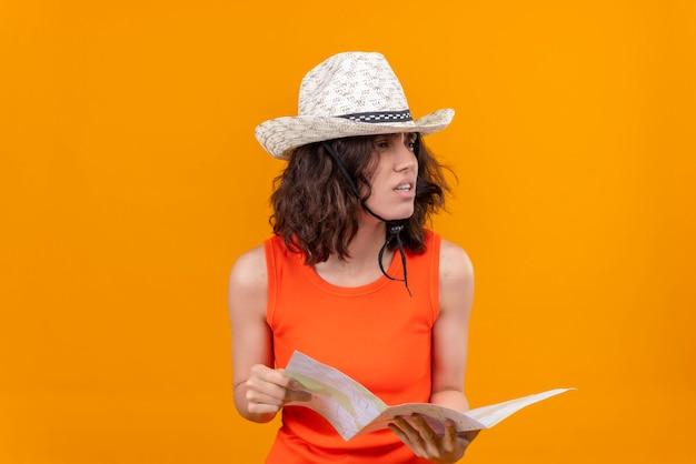 Молодая женщина с короткими волосами в оранжевой рубашке в шляпе от солнца держит карту и смотрит влево