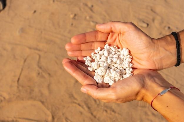 カナリア諸島、フェルテベントゥラ島の北にあるコラレホの町の近くのポップコーンビーチで石を手にした若い女性。スペイン