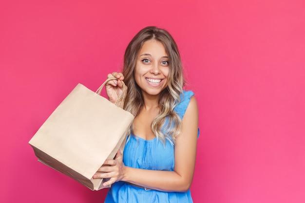 Молодая женщина с вьющимися волосами держит и демонстрирует бумажный эко-пакет с копией пустого места для логотипа