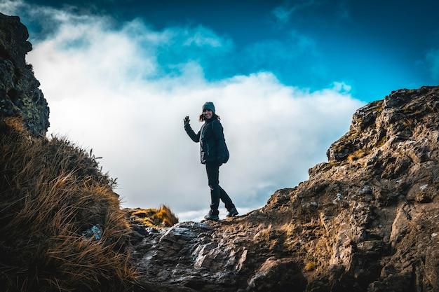 Молодая женщина в зимней шапке развевается на вершине горы аяко харриак, ойарцун. страна басков