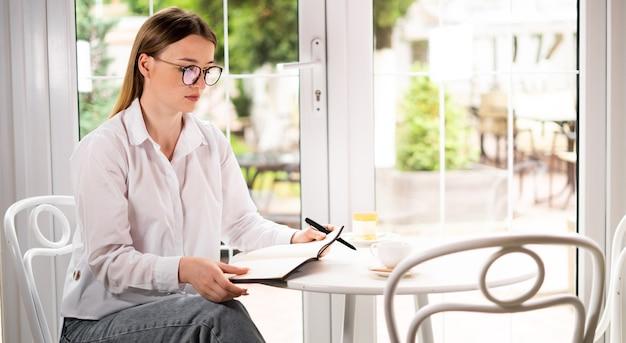 Молодая женщина, работающая в кафе с блокнотом, обдумывает идеи проекта, сидя у окна. студент в очках учится дистанционно в кафетерии. деловое утро и планирование дня.