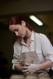 Молодая женщина, работающая в гончарной мастерской и выглядящая вовлеченной