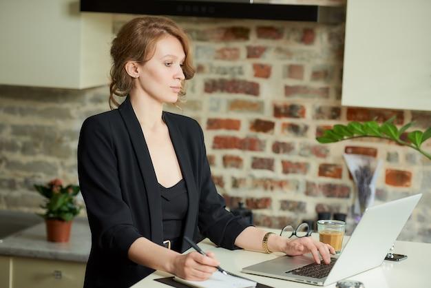 彼女のキッチンでリモートで作業する若い女性。自宅で従業員とテレビ会議中にニュースを探している女性の上司。