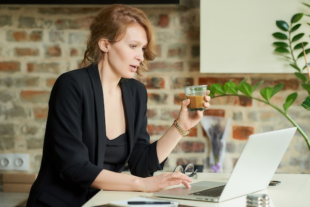 彼女のキッチンでリモートで作業する若い女性。自宅のビデオ会議で同僚とプロジェクトについて話し合うコーヒーを持つ女性の上司。