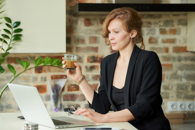 彼女のキッチンでリモートで作業する若い女性。自宅のビデオ会議で従業員とプロジェクトの議論を聞いているコーヒーを持つ女性の上司。