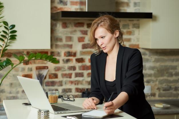 若い女性が彼女のキッチンで遠隔で働いています。ノートブックでメモを取り、自宅でビデオ会議中に同僚と話している魅力的な女の子。