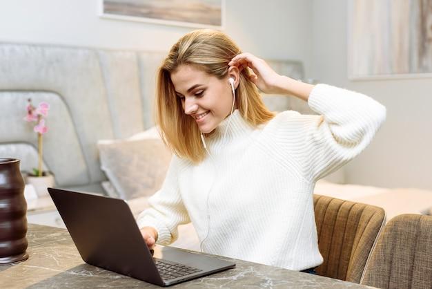 Молодая женщина работает с ноутбуком в своей квартире. коммерсантка-фрилансер в наушниках проводит деловую встречу из дома.