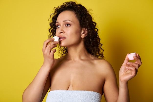 衛生的な口紅を使ってバスタオルに包まれた若い女性が、唇に潤いを与え、唇のケアをします。