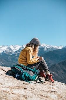 山の近くの丘に座って教科書を書いている若い女性